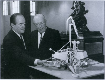 Photo of Hyland and Vice President Humphrey examining a model of Surveyor.